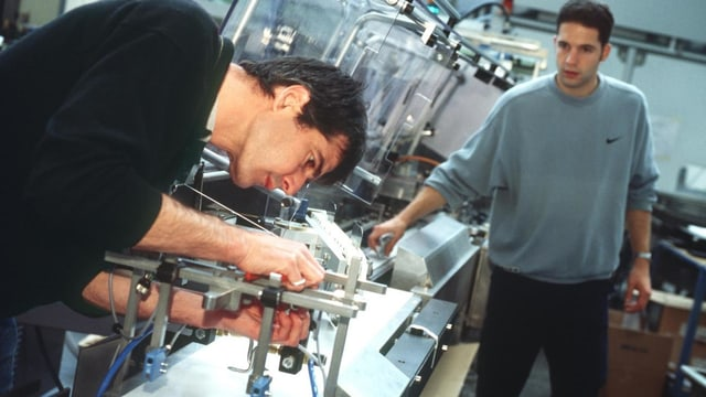 Techniker eines Verpackungsmaschinenherstellers testen und optimieren eine Verpackungsmaschine.