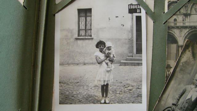 Ein älteres Foto zeigt ein Mädchen mit einem Kleinkind.