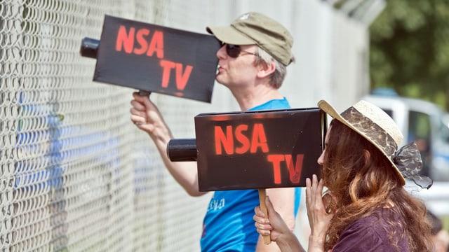 """Zwei Menschen mit selbst gebastelten Kameras auf denen """"NSA TV"""" steht."""