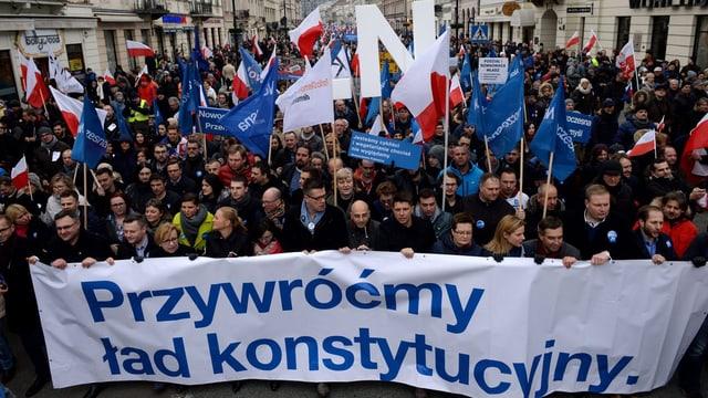 Demonstranten mit Transparenten in Warschaus Strassen