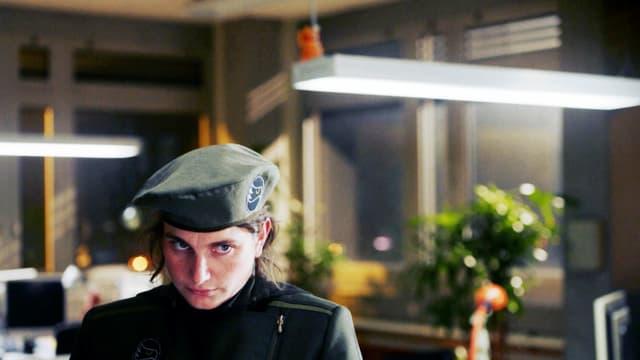 Eine Frau in Uniform steht in einem Büro.