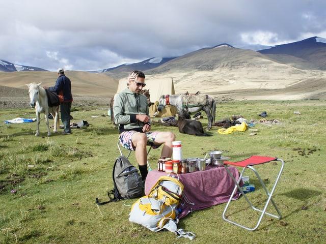 Andreas Thiel auf einem Campingstuhl beim Frühstück.