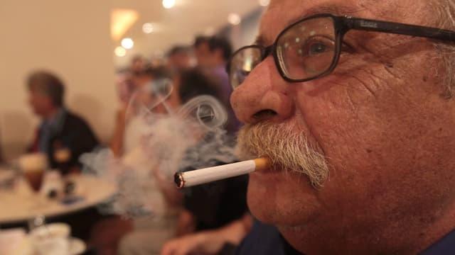 Ein älterer Mann raucht in einem Lokal eine Zigarette.