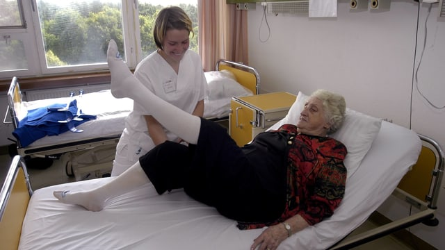 Pflegende hilft älterer Frau