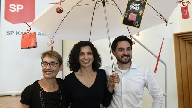 Drei Personen unter einem Schirm