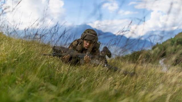 Rekrut liegt mit Waffe im Gras, dahinter Bergpanorama.