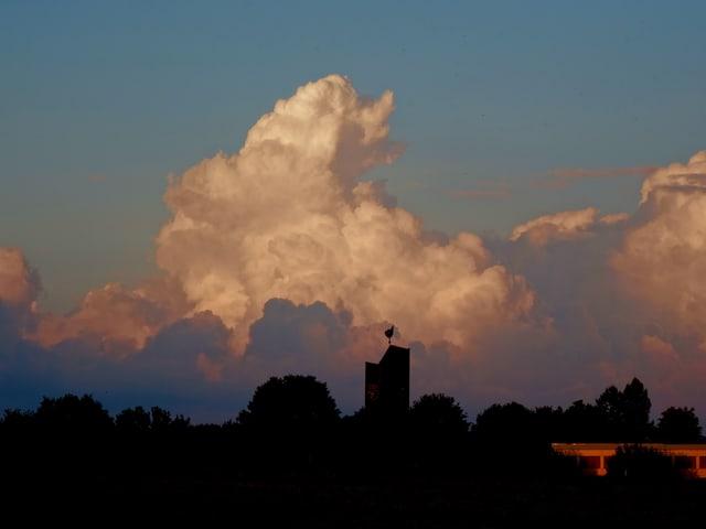 Im Vordergrund stehen ein paar Bäume und ein Kirchturm. Dahinter türmen sich grosse Quellwolken auf. In der Abendsonne erhalten die Wolken einen rötlichen Stich.