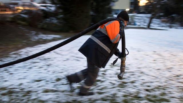 Ein Mann trögt einen Schlauch für Erdöl über eine verschneite Wiese.