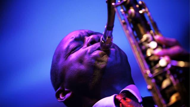 Branford Marsalis am Saxofonspielen, angestrengtes Gesicht, Bild in Blau-Violett-Tönen.