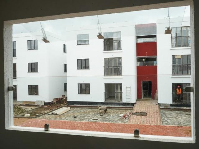 Blick aus Fenster auf dreistöckiges weisses Wohnhaus