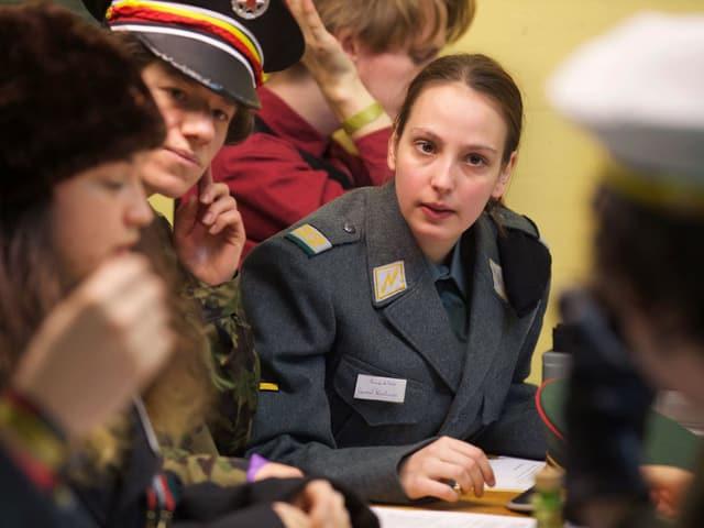Eine junge Frau im Offiziersmantel.