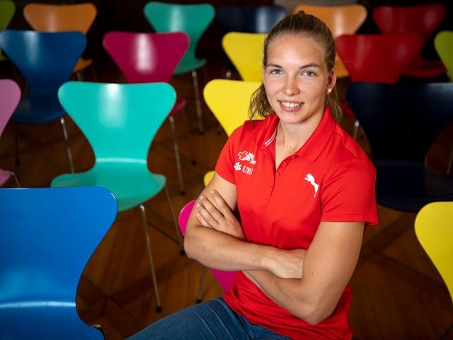 Géraldine Ruckstuhl sitzt mit verschränkten Armen auf einem farbigen Stuhl.