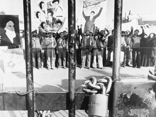 Die Besetzer der Boschaft durch das Gittertor fotografiert, an dem gut sichtbar eine Kette mit Schloss hängt
