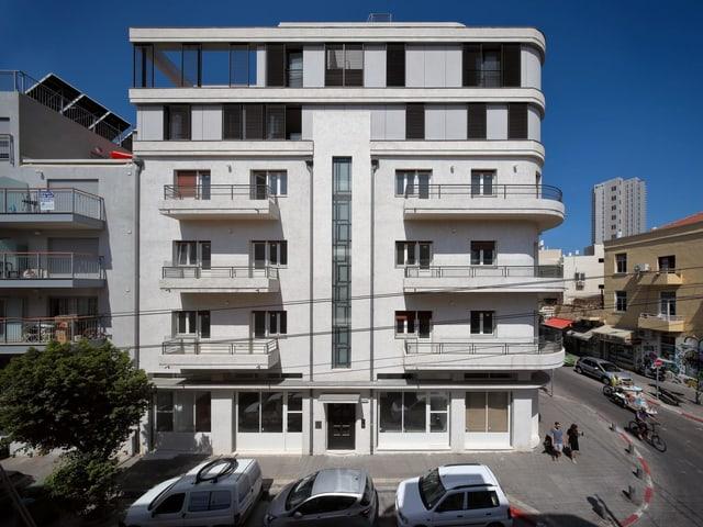 Ein weisses Gebäude. Unten im Bauhaus-Stil. Oben draufgebaut zwei moderne Stockwerke.