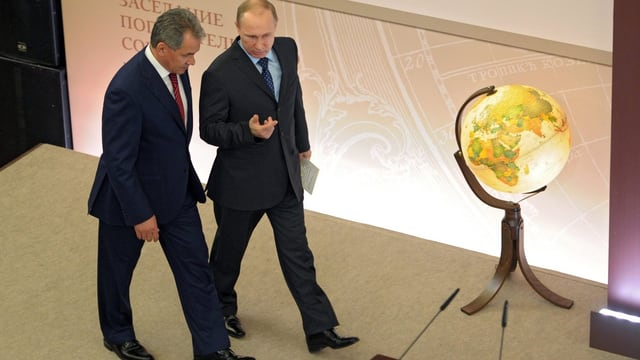 Putin und sein Verteidigungsminister gehen Seite an Seite an einem von innen beleuchteten Globus vorbei.