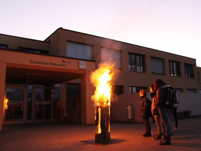 Kinder stehen vor einer brennenden Finnenkerze.