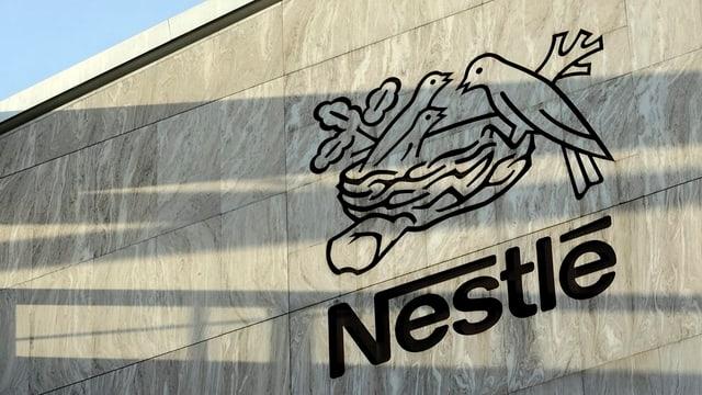 Das Firmenlogo von Nestlé an einer grauen Hausmauer.