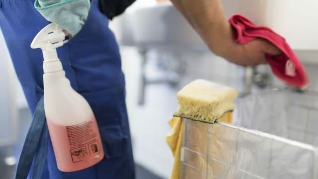 Ein Angestellter einer Reinigungsfirma putzt ein Wachbecken