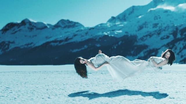 Zwei Frauen schweben über dem Schnee.
