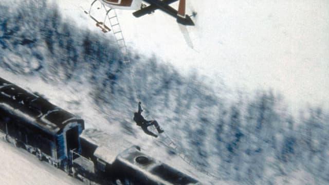 Ein Mann hängt an einer Strickleiter von einem Hubschrauber welcher über der Lokomotive eines Zuges fliegt.