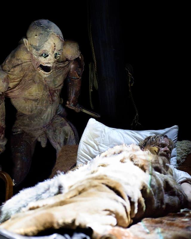 Monster-Puppe schleicht sich mit Messer in der Hand an schlafenden Mann heran.