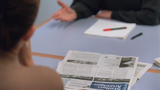 Eine stellensuchende Person im Gespräch mit einem Berater des Regionalen Arbeitsvermittlungszentrums (RAV)