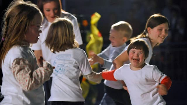 Ein Gruppe Kinder mit Down-Syndrom tanzt.