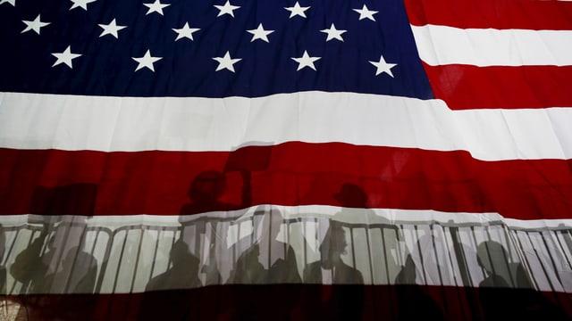 Menschen werfen Schatten auf die Flagge der USA.