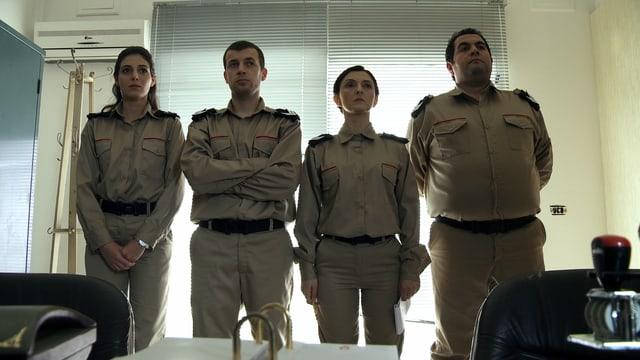 In olivgrüner Uniform stehen die Beamten der Zensurbehörde in Reih und Glied vor einem zugezogenen Fenster im Büro.