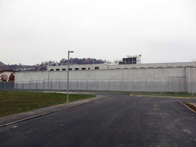 Eine asphaltierte Strasse führt zu einer hohen Betonmauer. Davor ein Zaun. Hinter der Mauer sieht man noch knapp den obersten Stock eines Gebäudes.