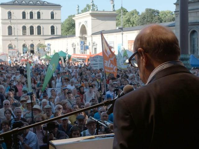 Jean Ziegler von hinten bei einem Auftritt vor einer grossen Menschenmenge.