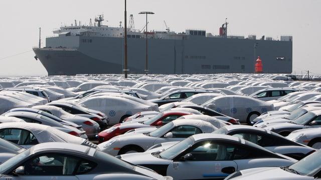 Neue Autos der Marke Volkswagen vor einem Transportschiff.