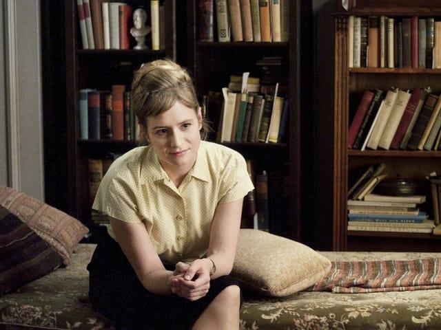 Die Schauspielerin Julia Jentsch sitzt auf einem Bett vor einem grossen Bücherregal und blickt freundlich aus dem Bild.
