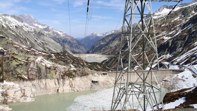 Fast leerer Stausee (Grimsel) im Hintergrund, im Vordergrund ein Strommast.