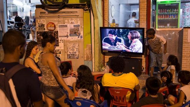 Kinder und Erwachsene versammeln sich draussen vor dem Fernseher und schauen die Telenovela.