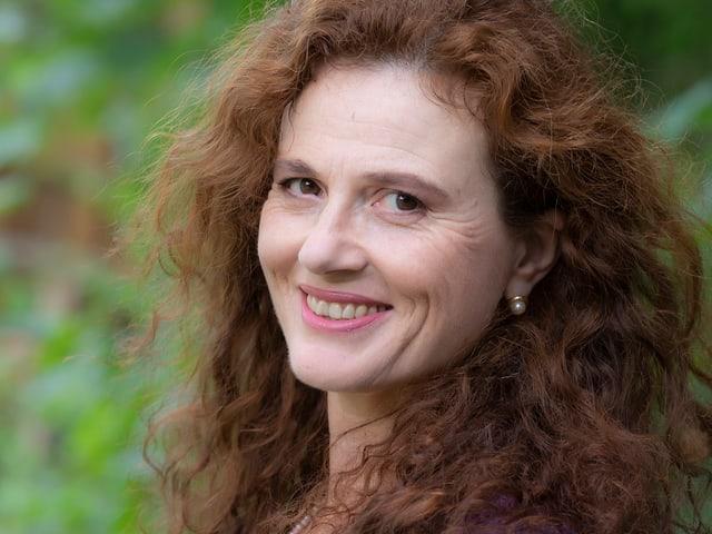 Eine Frau mit braunen Haaren lächelt in die Kamera.