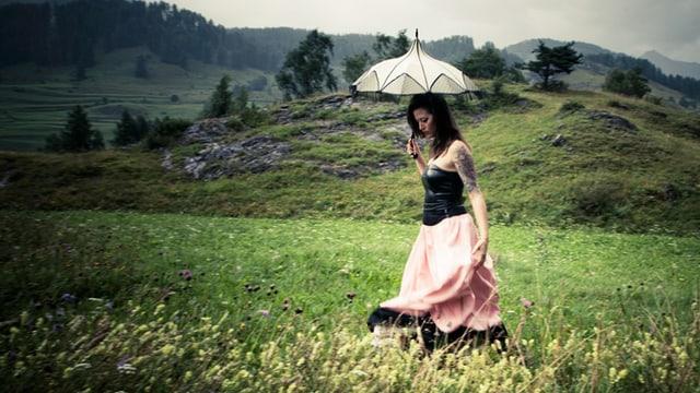 Die Sängerin Bibi Vaplan schreitet unter einem Sonnenschirm über eine Wiese.