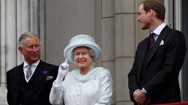 Queen auf einem Balkon, sie winkt. Daneben Charles und William.