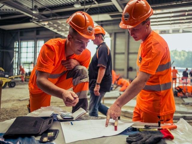 Arbeiter blicken auf Pläne