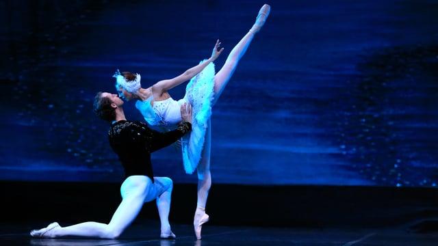 Ein Tänzer knieht und jhält eine Tänzerin an der Taille fest, das Paar küsst sich.