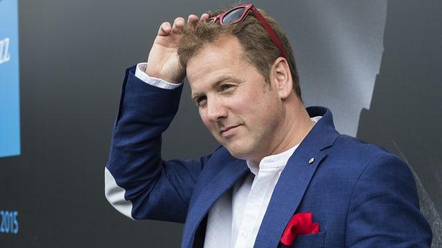 Ein Mann in blauem Anzug steht vor einem Werbeplakat und greift sich mit der Hand in die Haare, wo seine Sonnenbrille steckt.