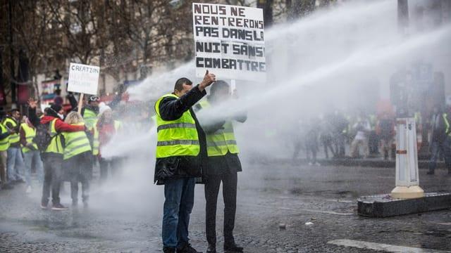 Männer mit gelben Westen und Plakaten.