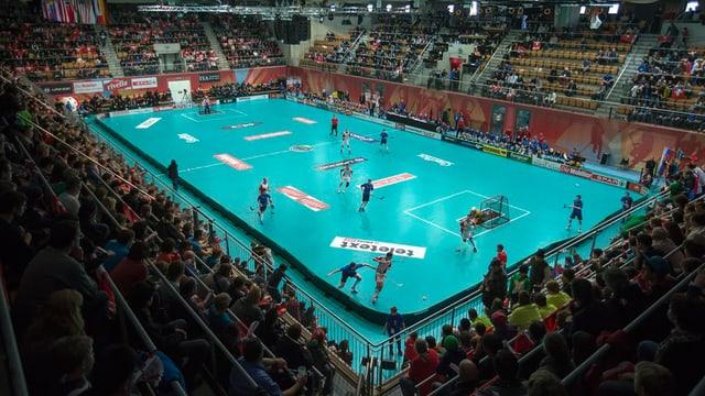 Sporthalle mit mehreren Unihockeyspielern