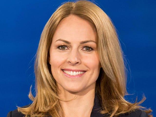 Eine blondhaarige Frau mit braunen Augen.