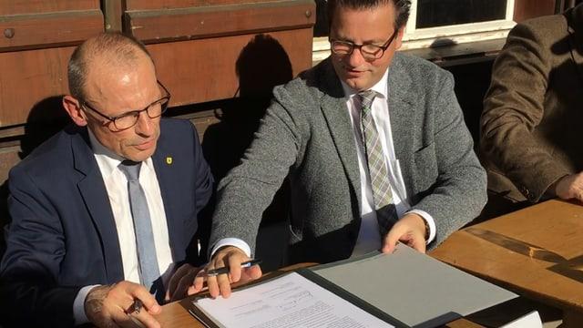 Zwein Männer in Anzug sitzen vor einem Vertrag, der auf dem Tisch liegt. Beide haben einen Stift in der Hand.