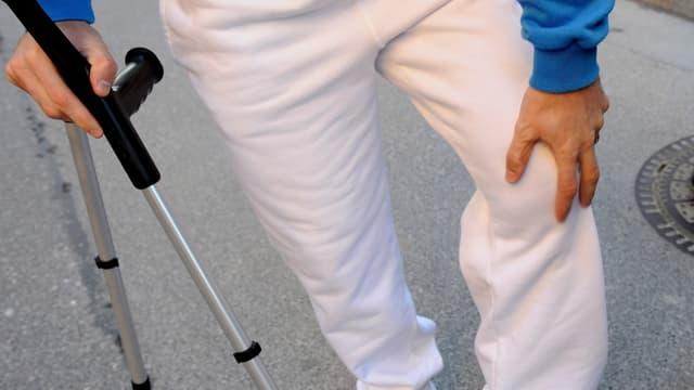 Mann in weisser Trainerhose, mit einer Hand hält er ein paar Krücken, mit der anderen fasst er sich ans Knie.