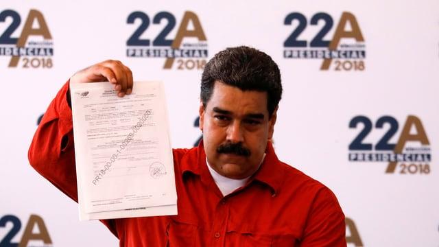 Nicolas Maduro, der ein Dokument in der Hand hält.