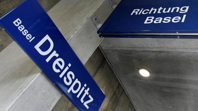 Nahaufnahmen der Hinweisschilder im Bahnhof Dreispitz. Auf einem blauen Schild steht Basel-Dreispitz, auf dem anderen Richtung Basel.