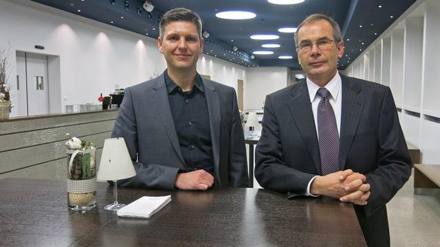 Zwei Männer in Anzügen stehen an einem Tisch.