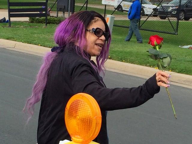 Frau mit violetten Haaren und einer Rose in der Hand